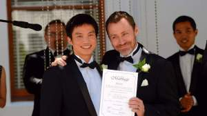 Marriage Equality director Ivan Hinton and Chris Tench display their marriage certificate in Canberra, before the High Court annulled them last week. Image attribution: sbs online